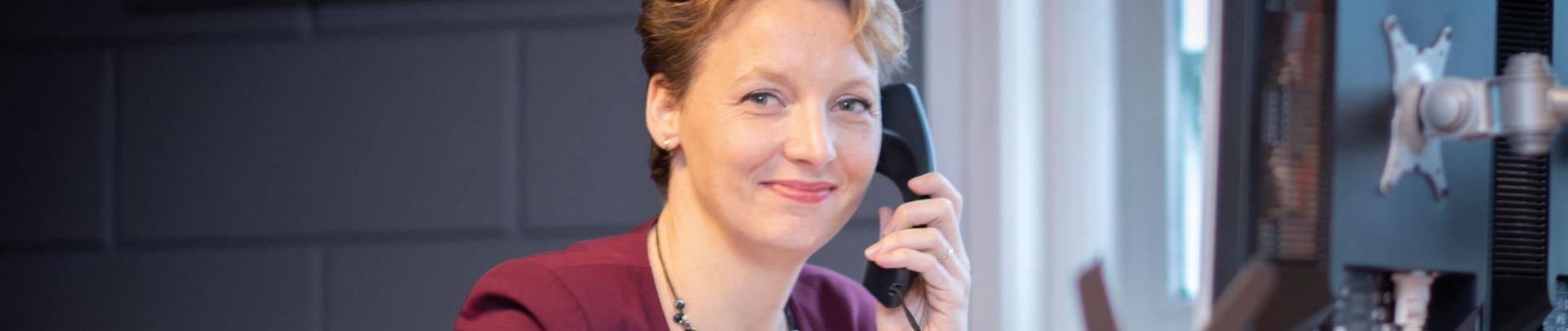 Trudy de Windt aan de telefoon achter haar computer
